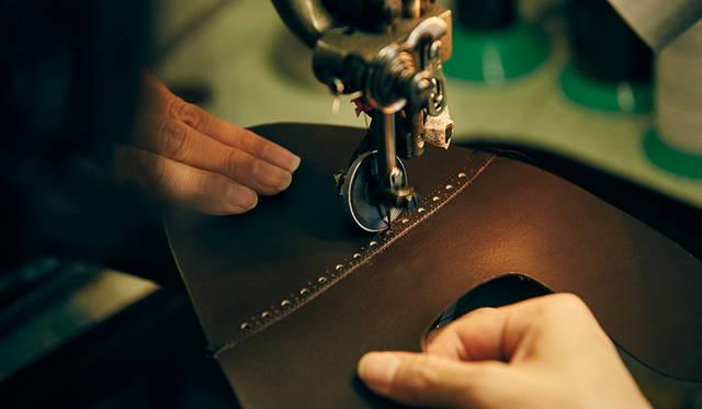 アッパーは専用ミシンを用い、一針一針ていねいに縫い合わせられる。羽根部分の強度を高めるカンヌキなどは、手で糸を編み込みながら縫うなど、各所に合った縫製を行う。なお、裁断や穴飾り、アッパー縫製などは繊細な作業を得意とする女性の靴職人がおもに担当している。