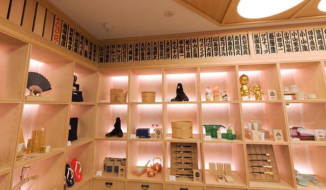 """全国各地の伝統工芸品や日用品、食品のほか、日本のクリエーションを紹介するイベントスペースが並ぶエントランスフロア奥には""""TEAM JAPAN""""メンバーの名前が木札になって飾られている"""
