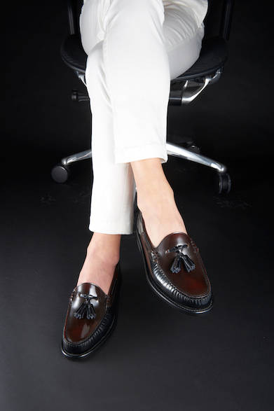 <strong>W56B</strong><br>22,000円(税別)<br>春夏、素足感覚で合わせたいタッセルスリッポン。光沢感ある甲革はブラックとダークブラウンのコンビネーション、ホワイトパンツに合わせ、スタイリッシュな履きこなしを。