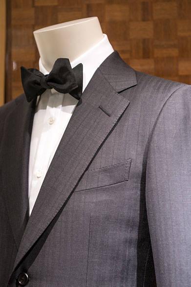 <strong>DUNHILL|ダンヒル</strong><br><br>ブランドのイメージをしっかり反映したスタイルは、ヘリンボーンにストライプの織りが入って、ブラックながら表情豊かな質感を醸し出している。カジュアルパーティにも着られるスーツとして活躍間違いなし。スーツ42万8760円、シャツ5万7240円、ボウタイ1万9440円