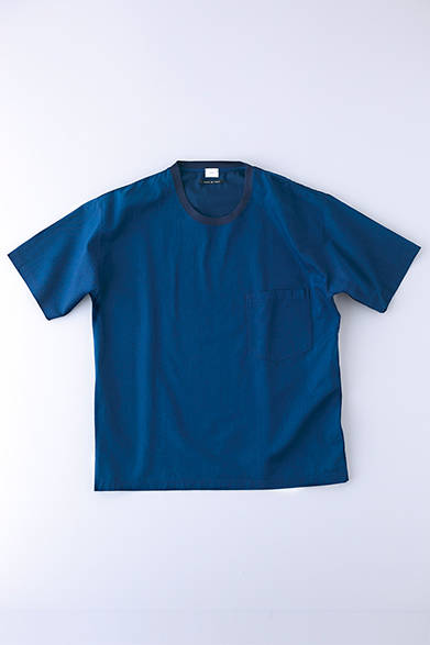 """シャツ地で仕立てたTシャツ。コシのあるコットンの生地感と、インディゴならではの風合いが魅力だ。インディゴの深みで変化をつけたトリムネックがアクセントの上品な一枚。Tシャツ2万円(コベルト)※税抜価格  <br /><br /><a href=""""/article/925192"""" class=""""link_underline"""">自分らしさを表現する春の装い 記事へ</a>"""