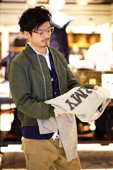 """「エヌリスト」のメンズラインの魅力を語ってくれた、メンズフロアのファッションアドバイザー・太田篤志郎さん。手に持っているのは、染み込みプリントで中央にARMYの文字を配したラグランスリーブのスウェット。V字のガゼットが前後に入るなど、ヴィンテージ風のディテールにも注目。スウェット3万7000円(エヌリスト)  ※税抜価格  <br /><br /><a href=""""/article/939788"""" class=""""link_underline"""">ファッションアドバイザーが語る「エヌリスト」</br>記事へ</a>"""