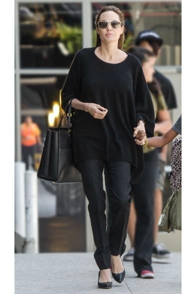 ロサンゼルス国際空港で女優のアンジェリーナ・ジョリーをキャッチ。緩やかなトップスに、大人カジュアルの定番アイテムであるテーパードパンツで構成されたフライトスタイル。ジョルジオ アルマーニのアイコンバッグと大ぶりのサングラスなど、上質な小物使いがオールブラックのコーディネイトにラグジュアリーな雰囲気をプラス。  Credit: Gonzalo Bauer