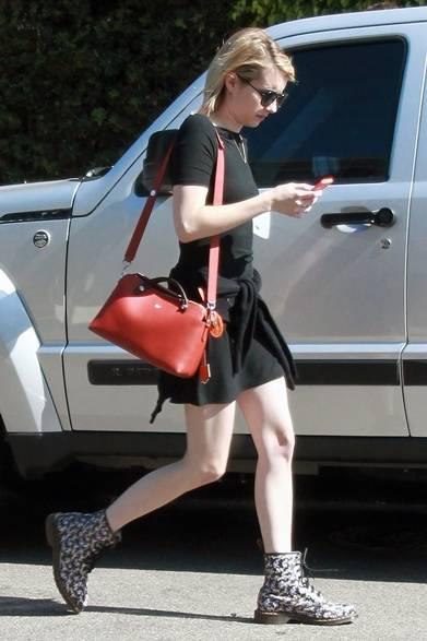 ハリウッドの街角に現れた女優のエマ・ロバーツ。ブラックのワンピースを着こなし、さりげない腰巻きのカーディガンがリラックス感を強調。赤いバッグと花柄のブーツがフェミニンなテイストを加えた。