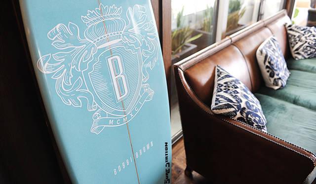ボビイブラウンのロゴが入ったサーフボード。この海の爽やかな雰囲気がボビイらしい世界を表している。
