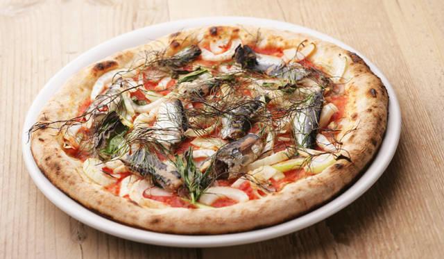 ピザは本場ナポリのピザ職人に支持されるカプート社の小麦粉を3種類ブレンドして作った生地に、ビールと相性のいい食材をトッピング。写真は北海道産真イワシのオイルサーディンにオレガノやフェンネルといったハーブで香りづけした「マリナーラ」(1600円)