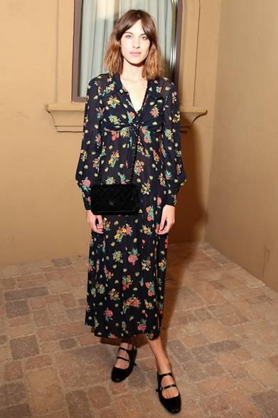 モスキーノのパーティでキャッチしたアレクサ・チャン。ノスタルジックな花柄を飾ったブラックのシフォンドレスに、シンプルなショルダーバッグとフラットシューズを取り入れたガーリースタイルを披露。