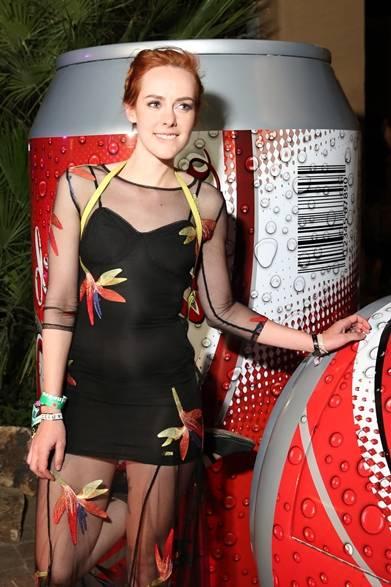 ポップなコーラ缶を前にポーズをとる女優のジェナ・マローン。繊細な刺繍を大胆にほどこしたシースルーのドレスが目を惹く。