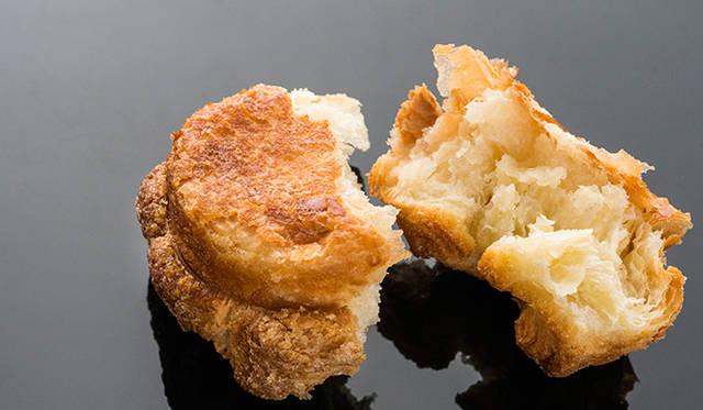 「DKA(ディーケーエー)」<br> ドミニク・クイニーアマンを意味する「ディーケーエー」は、フランスブルターニュ地方の伝統菓子「クイニーアマン」をベースに、ドミニク氏がオリジナルでレシピを開発。バターをたっぷり使ったリッチな風味のペイストリー生地を焼きあげて表面をキャラメライズ。カリッと香ばしく濃厚な味わいながらも甘さ控えめで、完璧なバランスに仕上げている。