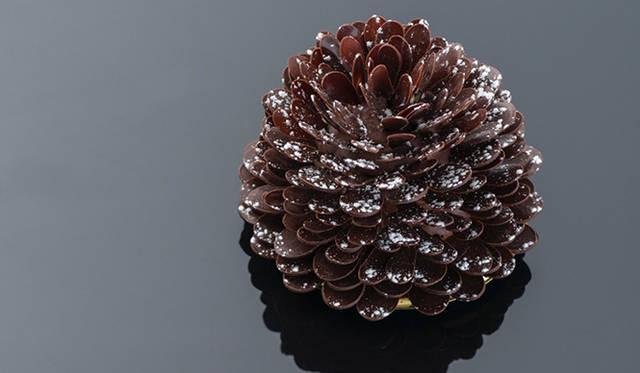 「ジンジャーブレッド パインコーン」<br> クリスマスツリーに飾る松ぼっくりのオーナメントからインスピレーションを受けたケーキ。ナツメグの香り高いケーキ生地に、ジンジャー風味のキャラメルクリームを挟み、チョコレートでコーティング。60以上のパーツから生みだされるケーキの見た目は、雪化粧をした松ぼっくりと瓜ふたつ。その完成度の高さに食べ方を躊躇うほどだ。