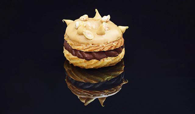 「パリス ニューヨーク」<br> リング状のシュー生地にクリームを挟む「パリ ブレスト」に、ドミニク氏がオリジナルでアレンジをくわえた「パリス ニューヨーク」。なかのクリームはピーナッツクリームとチョコレートのレイヤーで上品な味わい、表面はヘーゼルナッツ・アイシングで食感に変化をあたえている。ニューヨーク店オープン当初からあるメニューで、何度も改善され進化しつづけているメニューのひとつ。