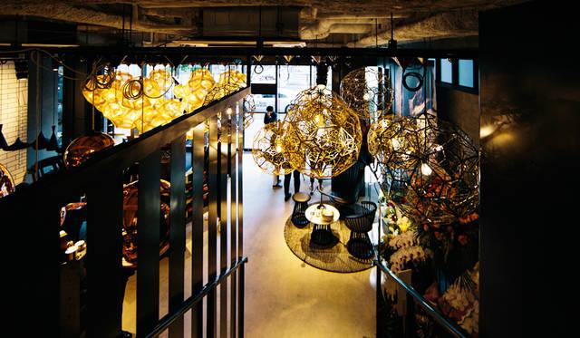 「TOM DIXON SHOP」店内の階段を上ってみると、天井から降りそそぐペンダントライトやシャンデリアの光が幻想的な風景を生み出している。左は「Etch Pendant Brass 32cm」を密集させた展示、右の「Etch Web Pendant」シリーズ