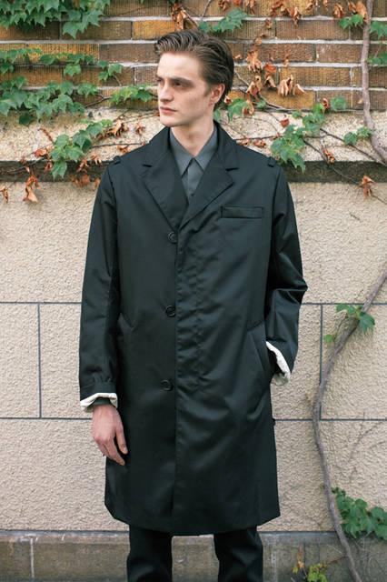 ナイロン素材のチェスターフィールドコートは、シングル仕立てで、前の合わせが深い独特なデザイン。ショルダーにはミリタリー感覚のループが付いていて、グレー色のコットンシャツと相まって、モダンマスキュリンな男性像をイメージさせる。 <br><br> コート24万4080円、デニム6万6960円、シャツ6万6960円[すべて予定価格](プラダ/阪急メンズ大阪2階)