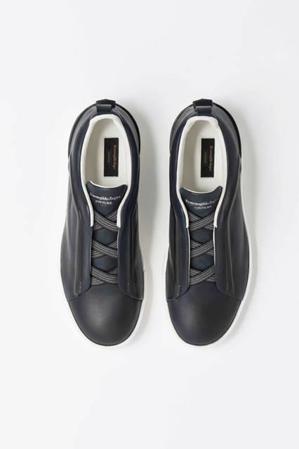 シューレースの部分にアイコンの「トリプルエックス」をあしらったスニーカーは手作業でインディゴ染めがほどこされたもの。ソールは日本製の黒ゴムと白のソールとなっている。靴9万7200円/エルメネジルド ゼニア
