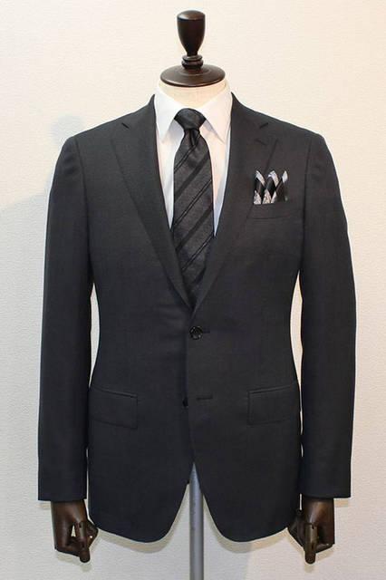 <strong>D'URBAN|ダーバン</strong><br />2015-16年秋冬コレクション 今季打ち出しのアムンゼン柄無地調スーツは、横糸にシルクを使用し、ソフトなシャンブレー感に光沢がくわわった生地が特徴。無地調のダークグレースーツに白無地シャツ、ブラック×グレーのレジメンタイ、3ピークのチーフというコーディネート。スーツ10万6920円