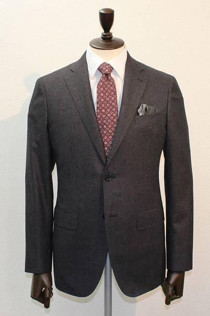 <strong>D'URBAN|ダーバン</strong><br />2015-16年秋冬コレクション SUPER140'S糸を使用した上質なフランネル素材のスーツ。ボルドーのカラー糸が表面に現れるカラーミックスが新鮮。無地調ブラウンのフランネルスーツにレッドのブロック柄ネクタイ、白無地シャツ、グレー×ブラックのチーフはパフというコーディネート。スーツ12万4200円