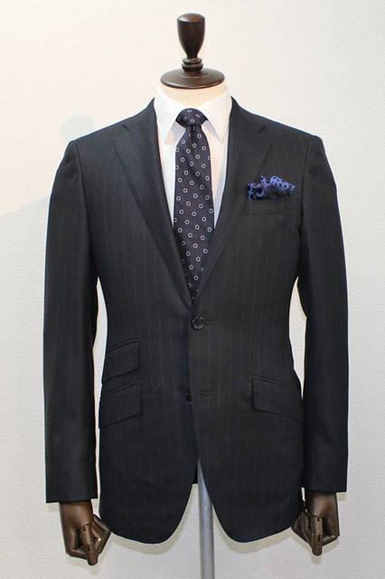 <strong>D'URBAN|ダーバン</strong><br />2015-16年秋冬コレクション 今季打ち出しのアムンゼン柄に17mmピッチのストライプをのせたスーツは、メインビジュアルでモデルが着用。ネイビーに白ストライプのスーツ、白無地シャツ、ブルーの○柄、ブルーの柄チーフというコーディネート。スーツ10万6920円
