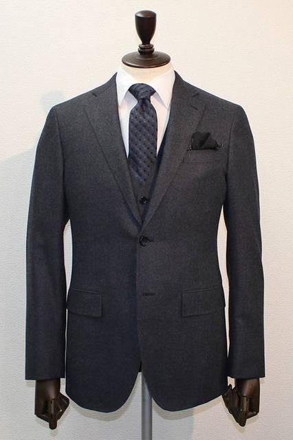 <strong>D'URBAN|ダーバン</strong><br />2015-16年秋冬コレクション SUPER140'S糸を使用し、極細原料をサキソニーで仕上げることでウール素材ながらデニム調に仕立てたスーツ。スリーピースの色味はブルーグレー、白無地シャツ、レジメン×ドット柄のダークブルータイ、ブラックのチーフというコーディネート。スーツ14万5800円