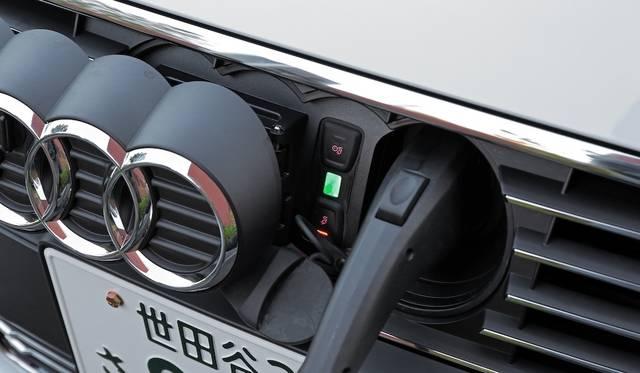 充電口は、フロントのアウディマークをスライドさせるとあらわれる。ソケットは日本仕様なので、既存充電設備の多くで利用が可能だという