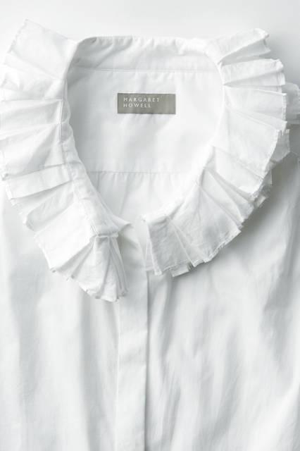 襟元のダブルラッフルがエレガントなシャツ。第一ボタンを外し、リラックスフィーリングで着こなすのがおすすめ。シャツ3万4560円
