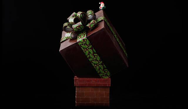 """<h2 class=""""cnt_subtitle"""">PALACE HOTEL TOKYO パレスホテル東京</h2>  ホテルメイドの上質な味わいと、目にも楽しいサプライズをお届け! クリスマス・イブにサンタが煙突に入りきらないほど大きなプレゼントを届ける様子を表現した「レーヴ」。すべてダークチョコレートでできたプレゼントボックスを開けると、キューブ型のチョコレートケーキとバニラのプティシューがお目見え。大人も子どももおもわず笑顔になる、遊び心と驚きが詰まった逸品だ。  <br /> <br />  <strong>「レーヴ」</strong><br /> 価格 2万1600円(15×30センチ)<br /> 予約受付中<br /> 引渡期間 12月20日(日︎)~25日(金)<br /> 引渡場所 パレスホテル東京 B1階「Sweets & Deli」<br /> 予約方法 電話、B1階「Sweets & Deli」 ※引渡の3日前までに予約が必要<br /><br />  <div class=""""article-contact""""> <div class=""""article-contact-head"""">問い合わせ先</div> <div class=""""article-contact-deta""""> <p class=""""article-contact-name"""">パレスホテル東京</p> <p class=""""article-contact-tel"""">Tel. 03-3211-5315(Sweets & Deli)</p> <p class=""""article-contact-url"""">http://www.palacehoteltokyo.com/restaurant/</p></div> </div>"""