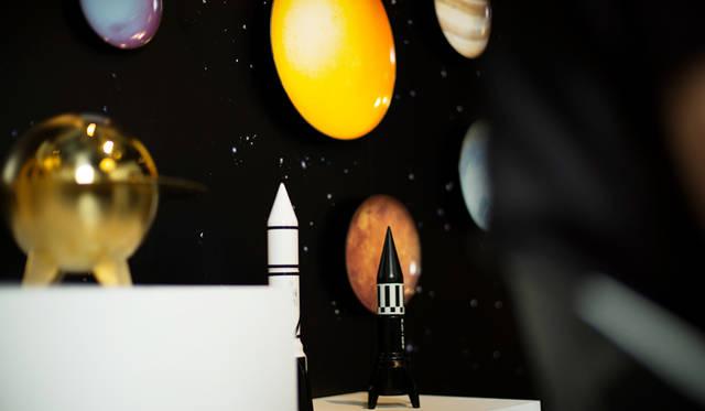 手前のロケット形のオブジェは、ソルト&ペッパーミル。1970年代に活躍したロケットのグラフィック、カラー、質感からインスパイアされている。背景に見える9つの惑星と太陽と月をモチーフにしたプレートと組みわせれば、宇宙空間にいるかのような世界がひろがる