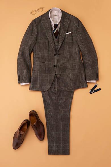 【モダン】 今季のトレンドであるチェック柄は3ピースで伝統的な正装を軸にコーディネートを考えたい。今回はスーツ地やインナーのシャツで格子柄や使用する色を合わせることで統一感を出している。あくまで装いは正統な着こなしにするのがポイント。そのため足元はブラウンのストレートチップを選んでいる。<br><br>モダンスタイル/スムースレザーブラウン<br>スリーピース12万円(ブリッラ ペル イル グスト)、シャツ2万5000円(エリッコ フォルミコラ)、ポケットチーフ2800円(ビームスF)、ネクタイ1万6000円(フランコ バッシ/すべてビームス ハウス 丸の内 03-5220-8686)、眼鏡6万4000円(10 アイヴァン/アイヴァン PR 03-6450-5300)、時計2万8000円(マーチ/エイチエムエスウォッチストア 表参道 03-6438-9321)