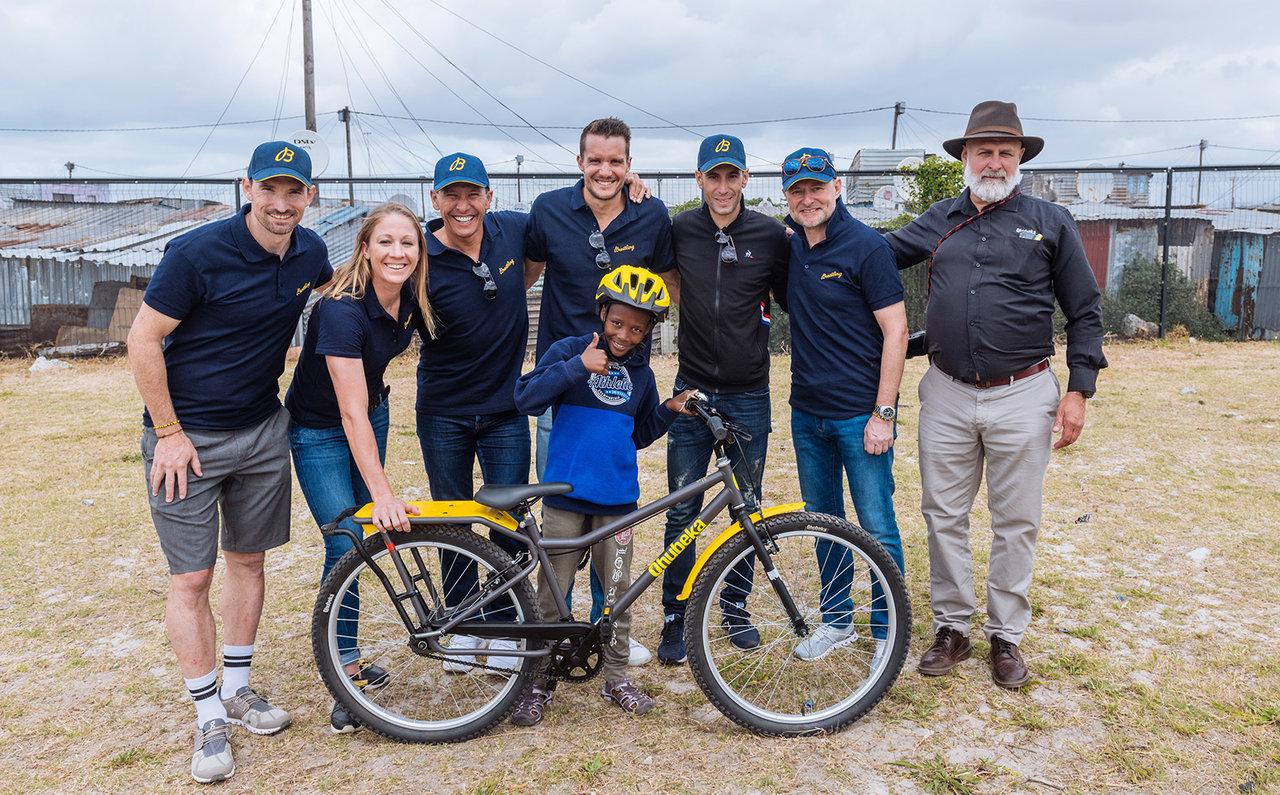 """レース翌日にはチームのメンバーにより100人の生徒に自転車を寄贈するセレモニーが開催された。自転車を贈られたウササゾ中学校の生徒と、後列は左からデュアスロンのスペシャリストであるロニー・シルトクネヒト、トライアスロン・スクワッドの3人ダニエラ・リフ、クリス・""""マッカ""""・マコーマック、ヤン・フロデノ、そしてイタリア人レーサーのヴィンセンツォ・ニバリとカーンCEO、クベカの創設者であるアンソニー・フィッツヘンリー。"""