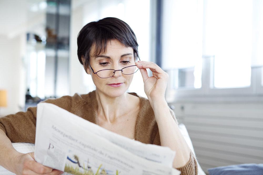 新聞を読む老眼の女性