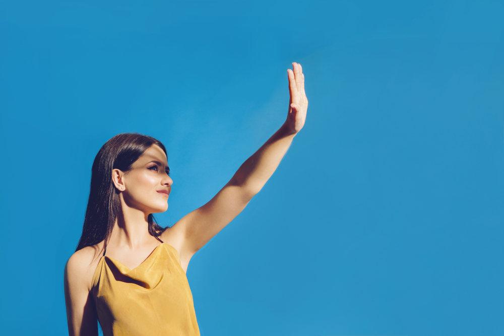 手で日差しを遮る女性