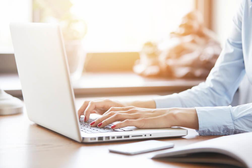 日の当たる場所でパソコンを打つ女性
