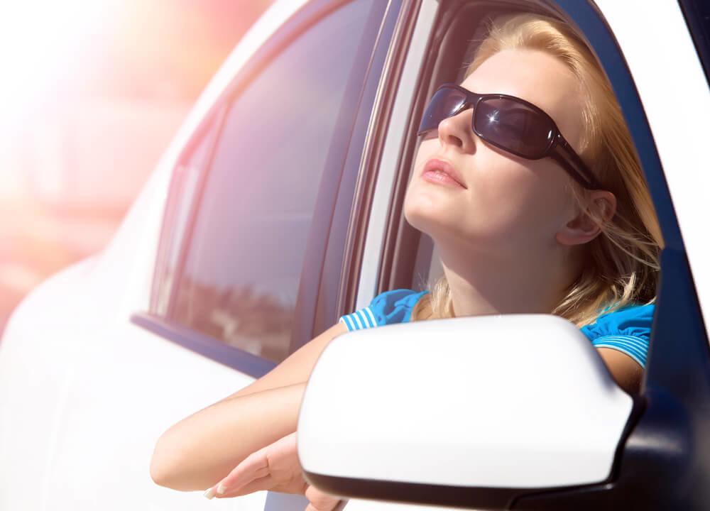 車の窓から太陽を見上げるサングラスの女性