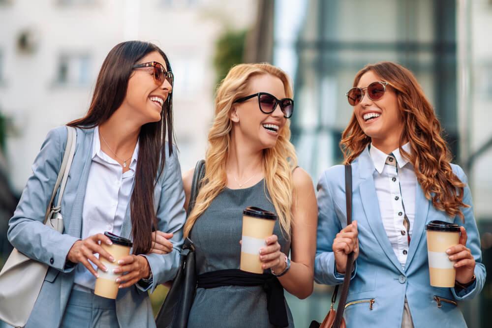 コーヒーを片手に談笑して歩く3人の女性