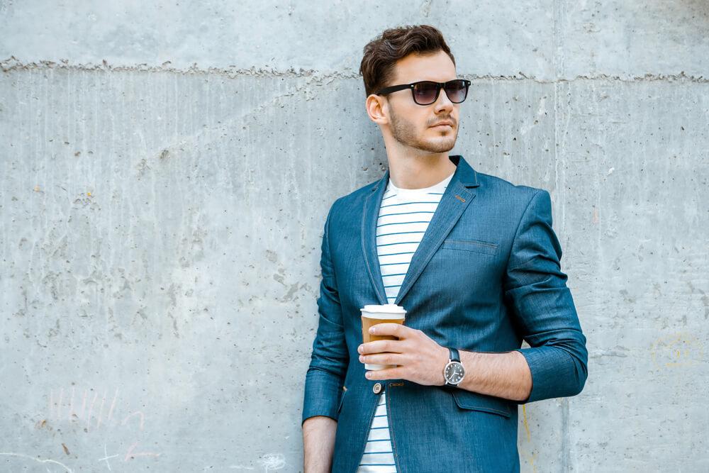 壁の前に立つサングラスの男性