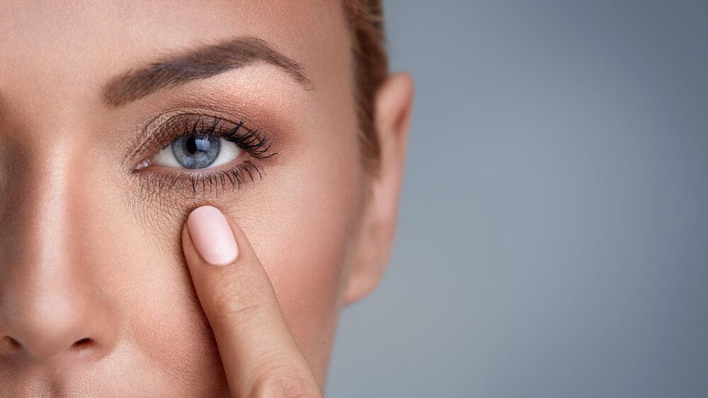 下瞼を抑える女性