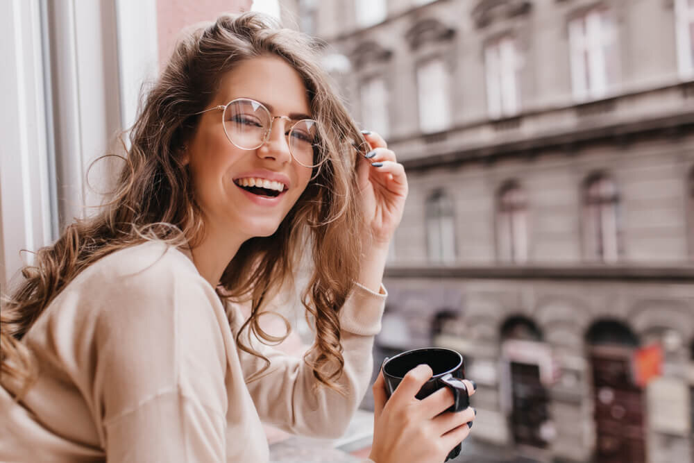 窓辺でマグカップを持って笑うメガネをかけた女性