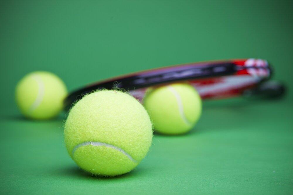 コートに置かれたテニスボールとテニスラケット