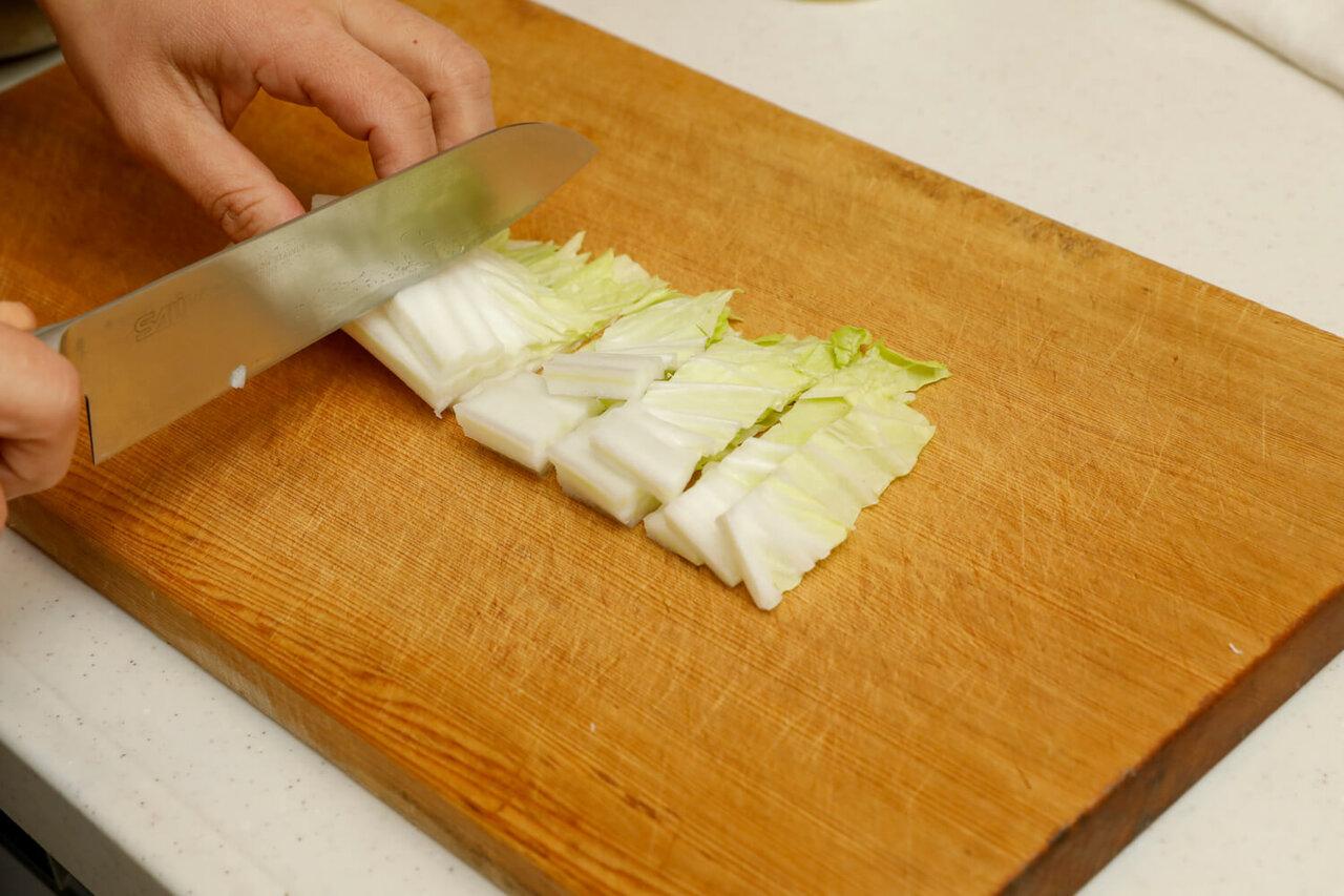 まな板の上の白菜を包丁で切る様子
