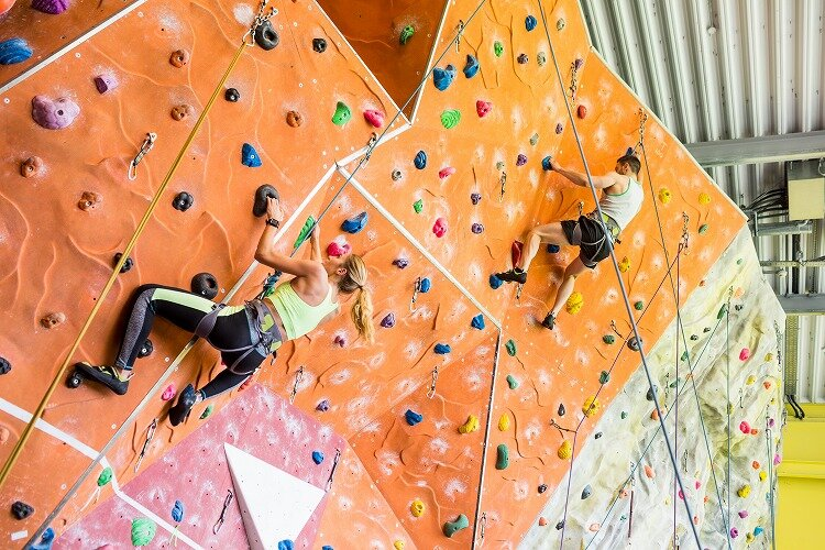 カラフルな壁を登るカップル