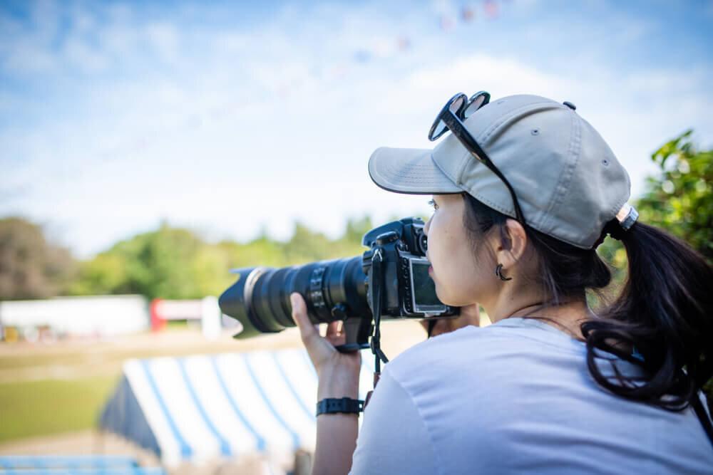 スポーツの試合会場でカメラを構える女性カメラマン