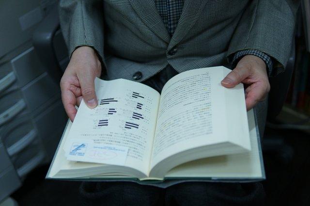たくさん専門書がある書棚から一冊の本を取り出して……