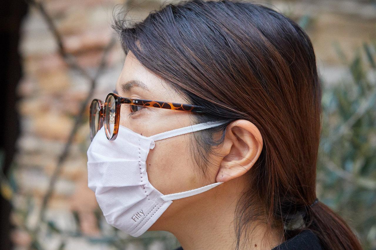 マスクの上部分を折り曲げてつける女性の画像