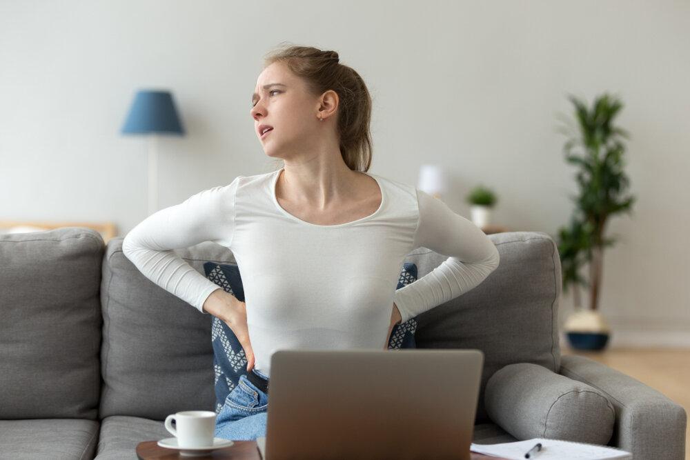 腰を抑えて腰痛に耐える女性
