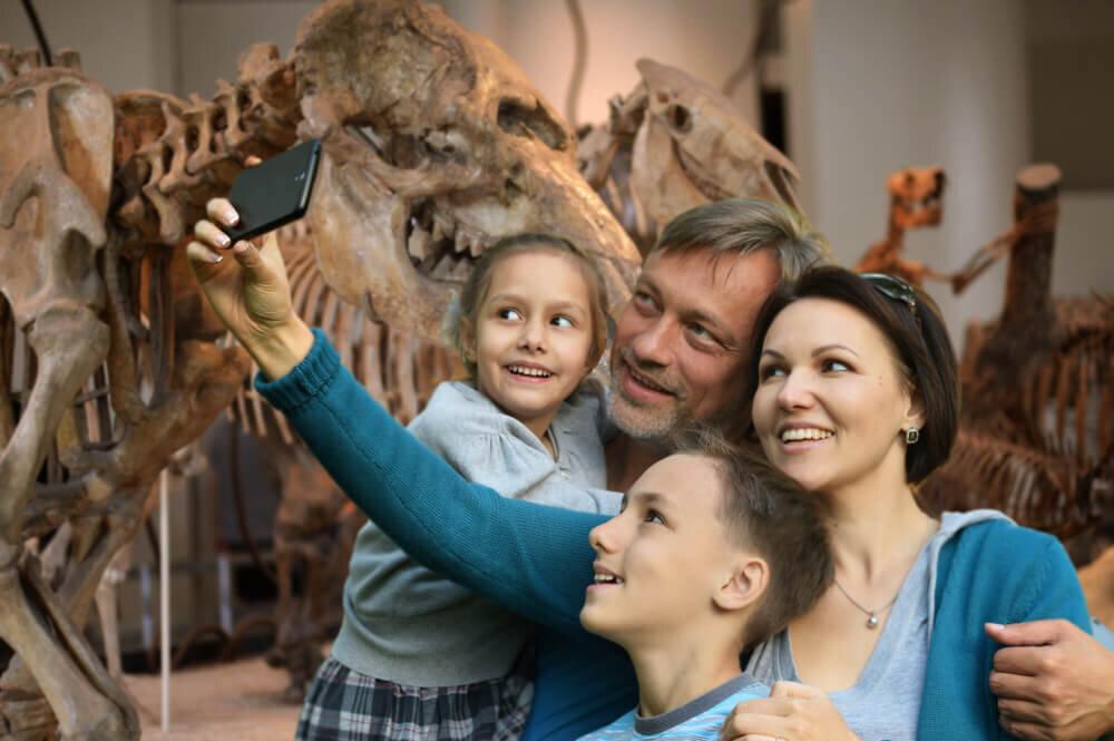 恐竜の骨の前で写真を撮る家族