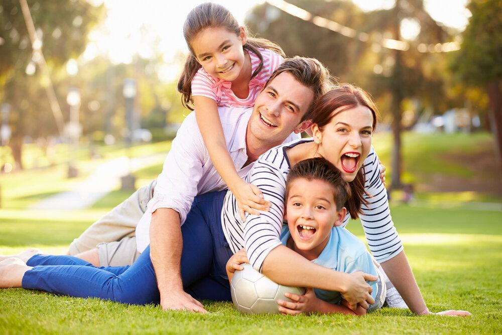 芝生の上で遊ぶ家族