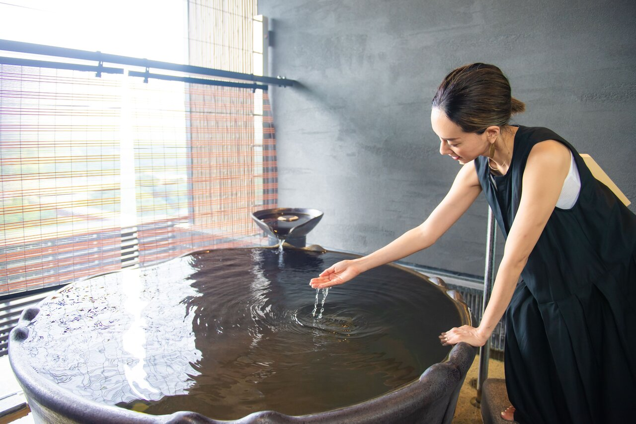 貸切風呂の湯加減を確かめる女性