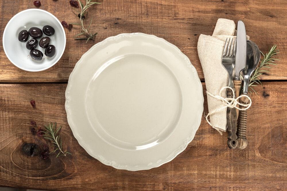 木のテーブルに置かれた皿とカトラリー