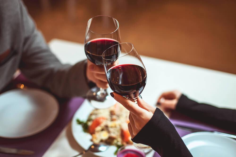 ワイングラスを傾けるカップル