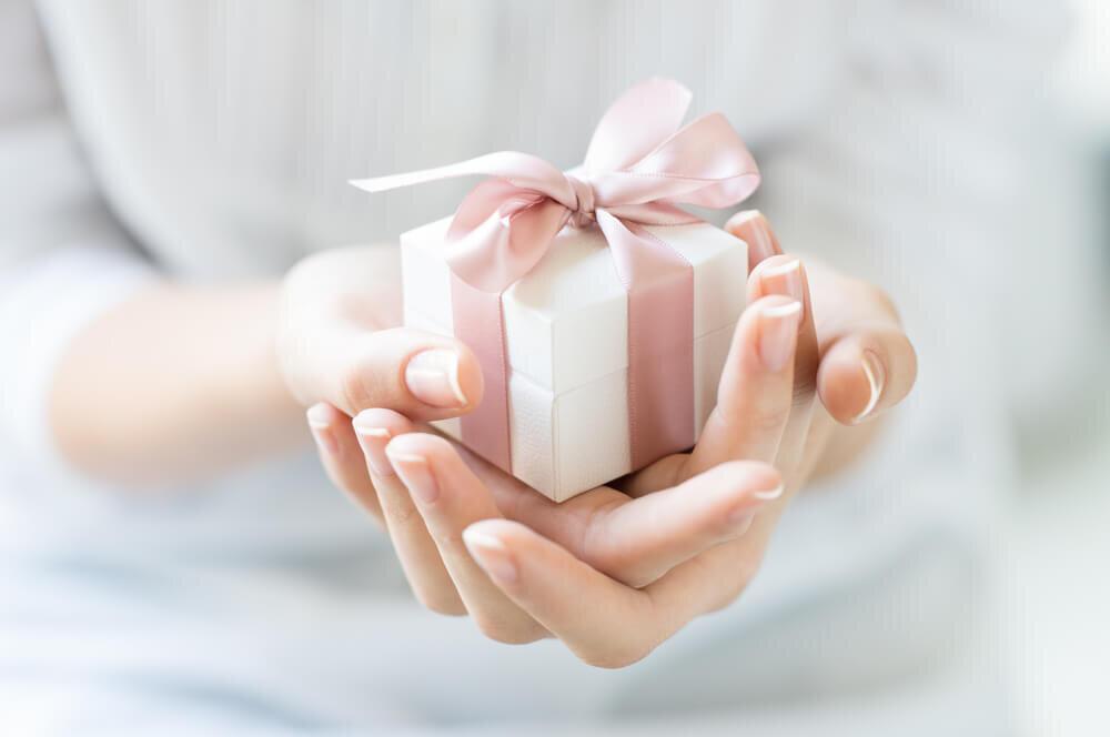ピンクのリボンのプレゼントを持つ女性