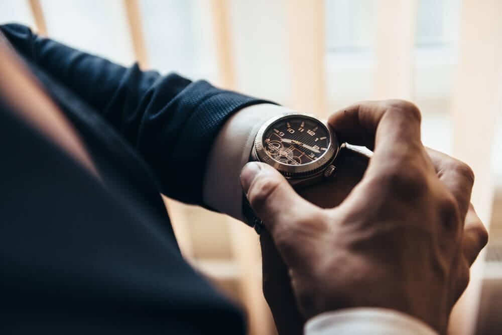 時計で時間を確認する男性